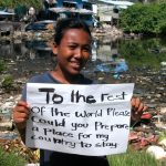 This Tuvaluan girl is holding her sign at a site she picked as an example of environmental degradation. Tuvalu is expected to become covered by the ocean in under 25 years, displacing the entire population.
