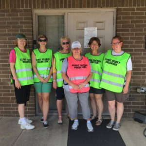 Clinic escorts wearing vests from the Clinic Vest Project bring women safely through lines of anti-abortion fanatics at an Arkansas clinic. Photo from The Clinic Vest Project.