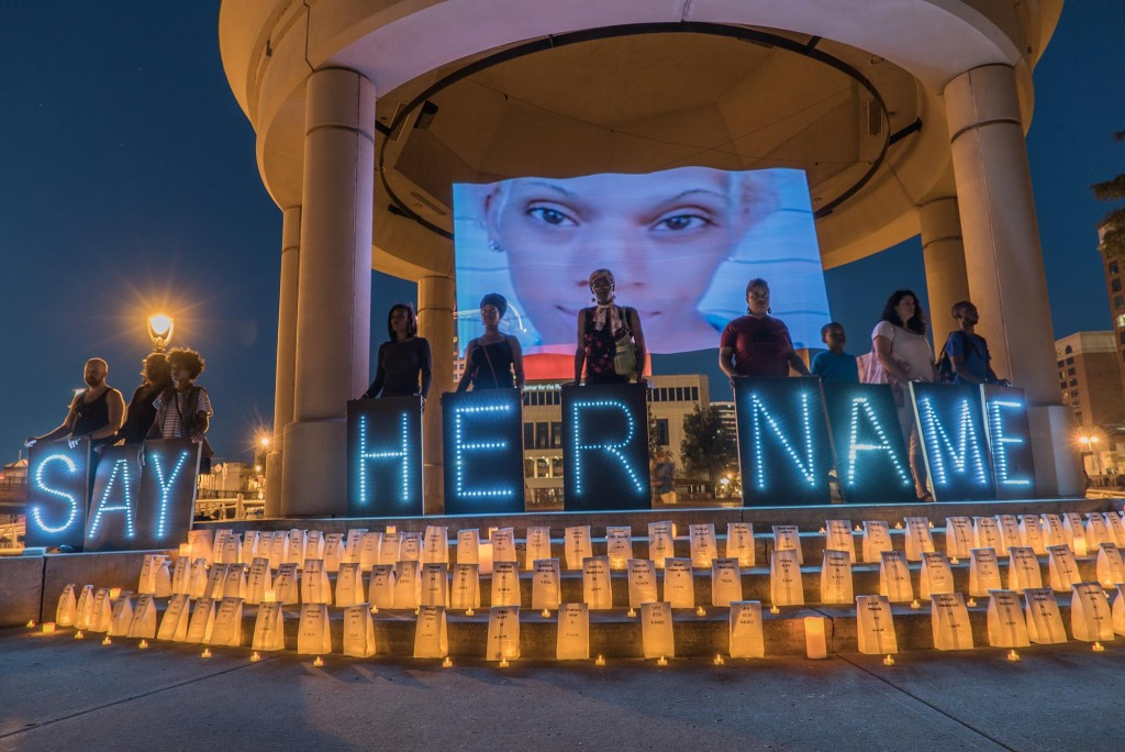 ug. 8 #SayHerName Milwaukee, Wisc., vigil for women slain by violence and hate. On the steps more women's names were illuminated by candles. Photo: Say Her Name Milwaukee