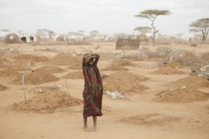A young girl stands amid the freshly made graves of 70 children many of whom died of malnutrition. Dadaab refugee camp, May 2017. Photo: Oxfam East Africa.